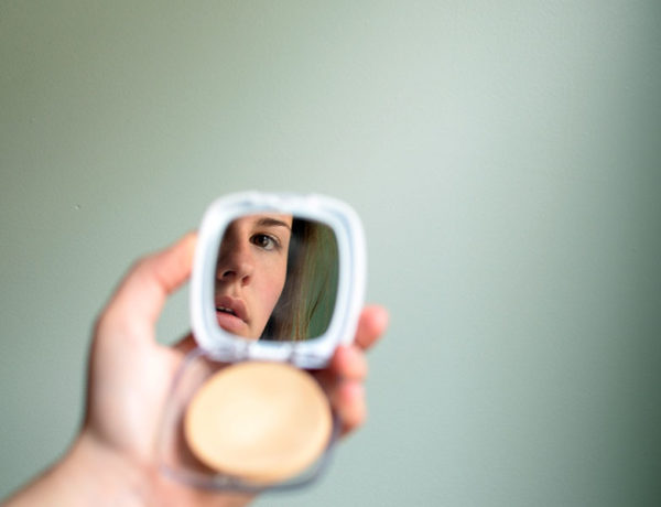 A woman who has body image issues, looking at her reflection in the mirror of her makeup compact.