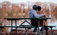 A couple sitting on a park bench.