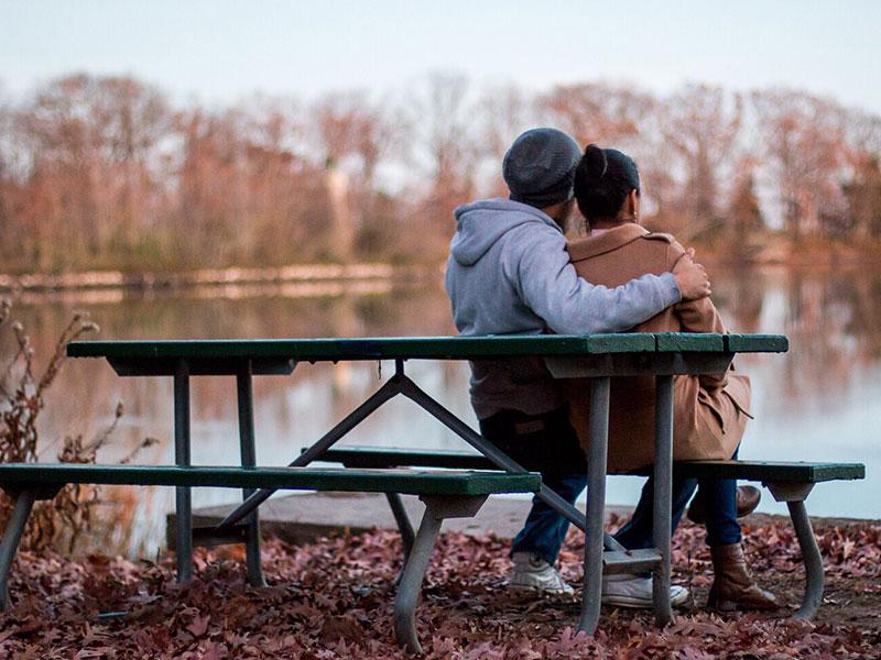 Un couple assis sur un banc de parc.