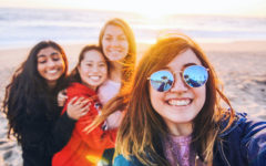 A group of girls who met on a Tinder for friends app, at the beach smiling as they take a picture.