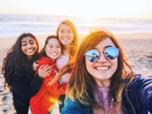 Un groupe de filles qui se sont rencontrées sur l'application Tinder for friends, à la plage, souriant en prenant une photo.