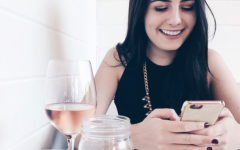 A woman laughing at her phone at one of these sweet pick up lines.