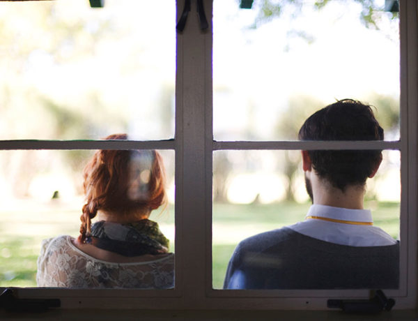 A man who has a fear of commitment sitting outside leaning against a window with her girlfriend as they have a discussion.