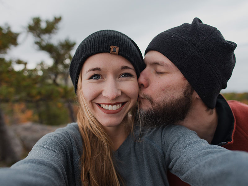 A couple who used to be in a situationship, smiling as the guy kisses the girl's cheek while hiking.
