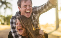 A couple who learned how to be friends with your ex, laughing in the sun while the woman gives the man a piggyback ride.
