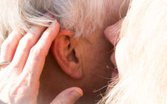 A woman whispering in her dates ear, after listening to some of these senior dating tips.