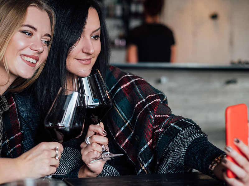 Two women who are bad friends smiling and taking a selfie together with wine.