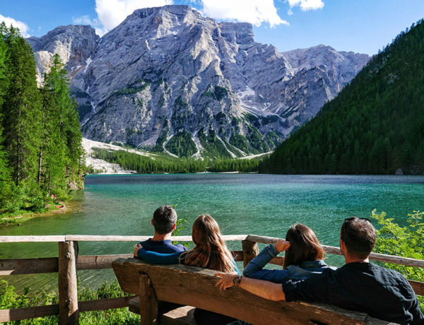 Four people in a quad relationship hanging out on a bench in front of a beautiful lake.