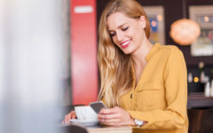 A woman on an online dating app at a coffee shop, smiling while on her phone.
