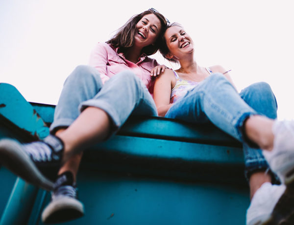 Two friends hanging out and smiling while sitting together outside.