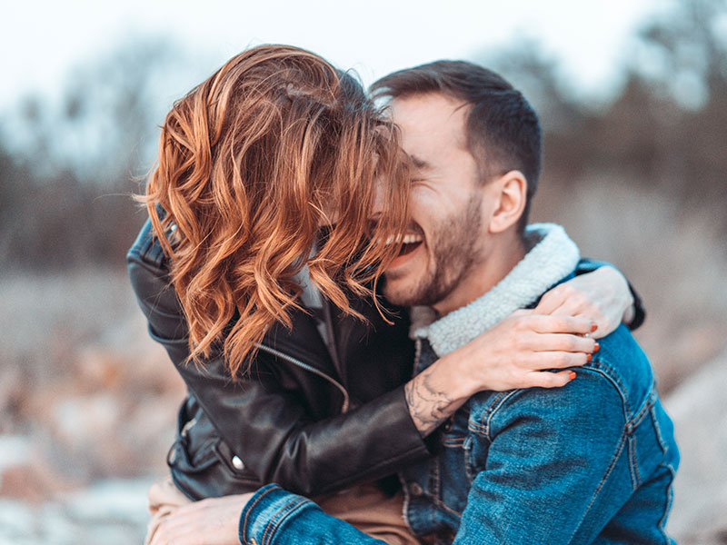 A couple who knows how to have good communication in relationships smiling and laughing outside as they hug.