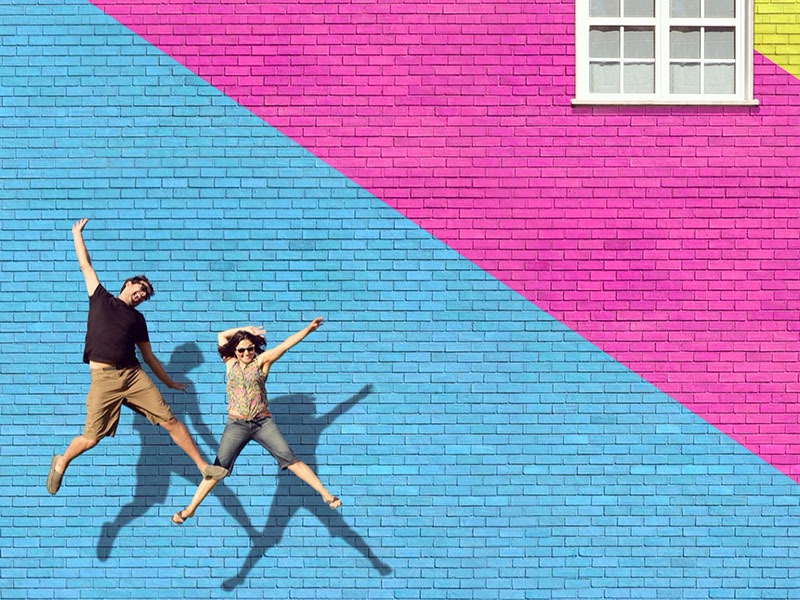Two happy people who never settled in love, jumping in front of a colorful wall.