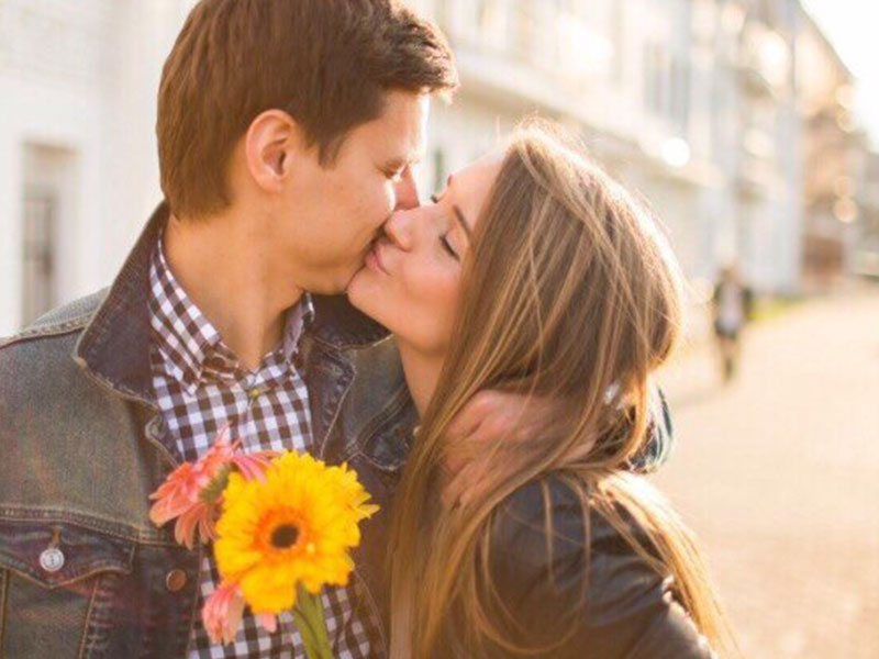 A guy who learned how to woo someone, kissing his girlfriend while holding flowers.