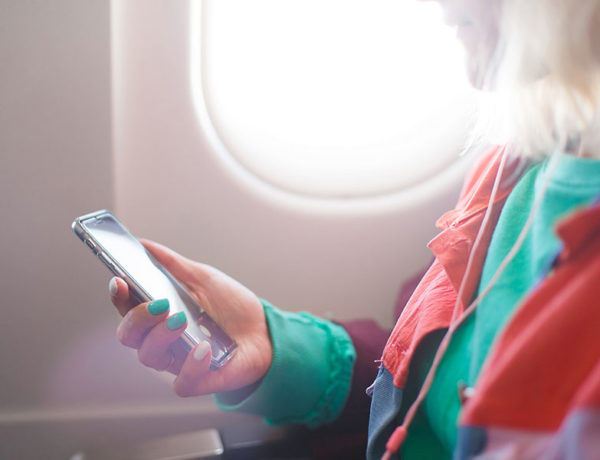 A girl listening to one of the best relationship podcasts on her phone while on a plane.