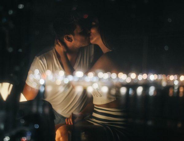 couple kissing under fairy lights having a Tinder hook up
