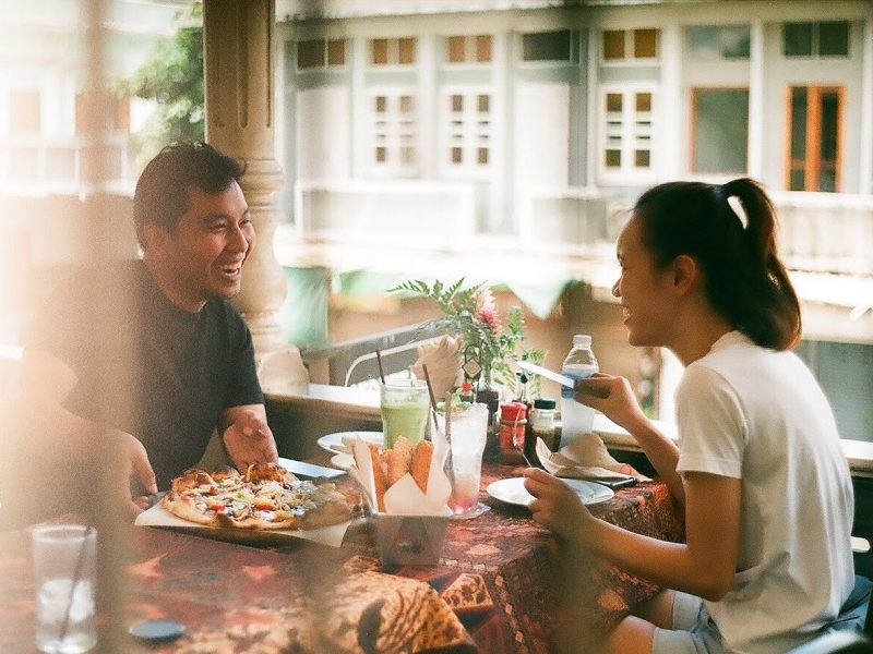 man and woman practicing good first date etiquette while eating pizza