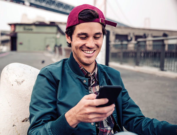 Smiling man checking his smartphone for new messages