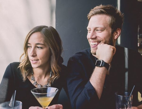 Couple dating at 40, enjoying cocktail and looking out the window together
