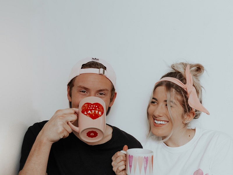 Cute couple laughing and drinking coffee while enjoying unconditional love