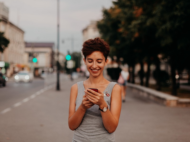 Attractive young woman smiling while using correct Tinder etiquette on her mobile phone